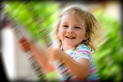 Happy child on swing. Closeup of happy preschool girl on swing with slow motion blur Royalty Free Stock Images
