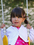 Happy Child on Swing. Close up of happy little Hispanic girl swinging on a swing. Focus on child's face Stock Photography