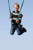 Happy child on a swing. Happy child playing on a swing Royalty Free Stock Image