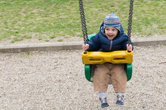 Happy child on swing. In pablic park royalty free stock photography