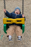 Happy child on swing. In pablic park royalty free stock photo