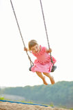 Happy child on swing in summer Stock Images
