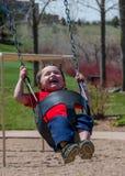 Happy child swinging Royalty Free Stock Image