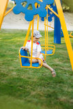 Happy child swinging on a swing Royalty Free Stock Image