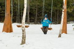 Happy child on swings at a winter park stock images