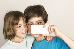 Happy child take a selfie. Happy child doing a squint and taking a selfie with a smartphone at home  on white background Stock Images