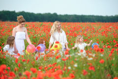 Happy child and teens running in the poppy field Stock Photos