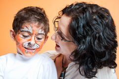 Happy child in tiger make-up and mother Stock Images