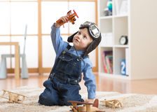 Happy child toddler playing with toy airplane and dreaming of becoming a pilot Stock Photography