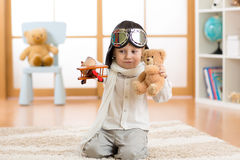 Happy child toddler playing with toy airplane and dreaming of becoming a pilot Stock Images