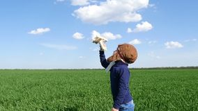 Happy child with toy airplane at sunset in the field. Child having fun outdoors. The concept of imagination and freedom stock video