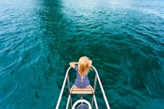 Happy child traveling on sailing yacht. Joyful child portrait. Happy little baby girl on board of sailing yacht have fun discovering islands in tropical sea on Stock Photo