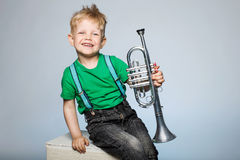 Happy child with trumpet. Happy little boy smiling and holding trumpet Royalty Free Stock Photography