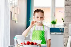 Happy child trying sweet dough from the mixer beater. After mixing for cake. Child helping in kitchen Stock Images