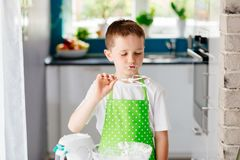 Happy child trying sweet dough from the mixer beater. After mixing for cake. Child helping in kitchen Royalty Free Stock Images