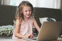 Happy child using laptop at home. School girl learning with computer and internet Stock Image