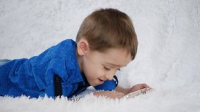 Happy child is using a smartphone for games, lying on a white sofa stock footage