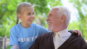Happy child volunteer hugging male pensioner smiling each other, old people care stock video footage