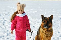 Happy child on a walk with dog in winter. Girl on a winter walk with the dog Royalty Free Stock Photos