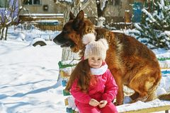 Happy child on a walk with dog in winter. Girl on a winter walk with the dog Royalty Free Stock Images
