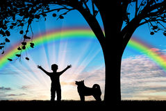 Happy child walking with dog near tree on background of rainbow. Friendship and happiness concept Royalty Free Stock Photo