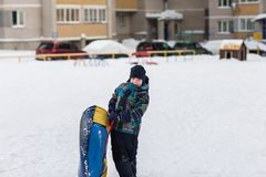 Happy child walks with tubing in the winter frosty day stock photography