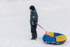 Happy child walks with tubing in the winter frosty day Stock Images