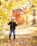 Happy child in warm clothes running through the forest Stock Image