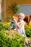 Happy child watering flowers Stock Images