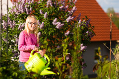 Happy child watering flowers in  the garden Royalty Free Stock Image
