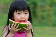 Happy child with watermelon. Little Asian kid with a piece of watermelon in park Stock Photography