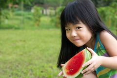 Happy child with watermelon. Little Asian kid with a piece of watermelon in park Stock Images