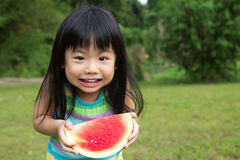 Happy child with watermelon. Little Asian kid with a piece of watermelon in park Royalty Free Stock Image