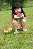 Happy child with watermelon. Little Asian kid with a piece of watermelon in park Royalty Free Stock Images