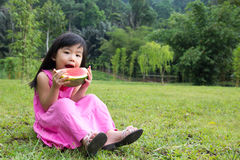 Happy child with watermelon. Little Asian kid with a piece of watermelon in park Royalty Free Stock Photos