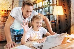 Happy child waving while having a video talk. Hello. Cheerful smiling boy waving to the web camera and having a video talk while his attentive kind father stock photos