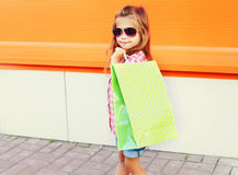 Happy child wearing sunglasses with shopping bags walking in city Royalty Free Stock Photography