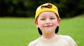 Happy child wearing yellow ball cap Stock Photos