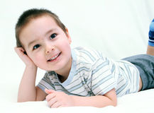 Happy child on white bed Stock Photography