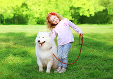 Happy child with white Samoyed dog on the grass Royalty Free Stock Image