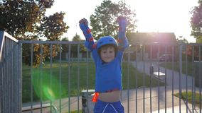 Happy child winner, boy in roller skates and helmet raises hands up on rollerdrome outdoors stock video