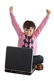 Happy child winner sitting with a laptop Royalty Free Stock Images