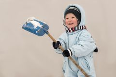 A happy child in winter fashion clothes is cleaning the snow with a shovel in the courtyard of his village house. Family, traditio. N, holiday Royalty Free Stock Image