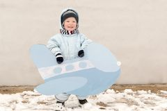 Happy child in winter fashion clothes posing with a toy airplane in the courtyard of his village house. First snow, family, tradit. Ion, holiday Royalty Free Stock Image