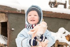 A happy child in winter fashion clothes posing with a toy pig in the courtyard of his village house. First snow, family, tradition. Holiday Stock Photography