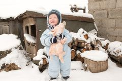 A happy child in winter fashion clothes posing with a toy pig in the courtyard of his village house. First snow, family, tradition. Holiday Royalty Free Stock Image