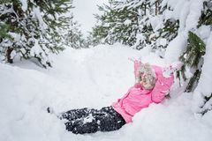 Happy child in winter pine forest. baby girl in a pink jacket throws snow outdoor.  stock image