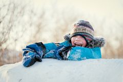 Happy child in winterwear laughing while playing in snowdrift Royalty Free Stock Photos