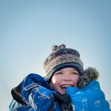 Happy child in winterwear laughing while playing in snowdrift Stock Image