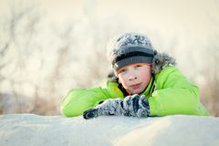 Happy child in winterwear smiling while playing in snowdrift Stock Image